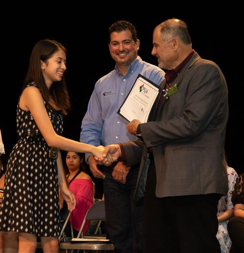 PSJA Southwest Early College High School graduate Dioselina De La Cruz receives her scholarship from PSJA Board and Foundatio